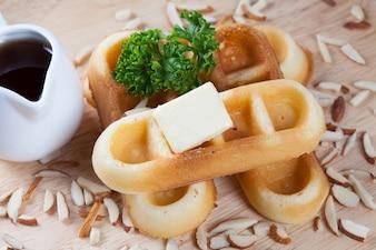 Close-up cialde e dado con prezzemolo e formaggio in cima a cialde su piastra di legno per la prima colazione.