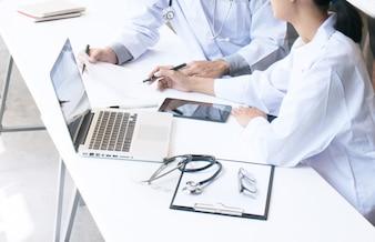 Close up di paziente e il medico che prende appunti o medico professionista in uniforme bianco uniforme cappotto intervista