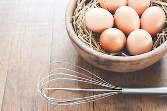 Close-up di uova di pollo grezzo in ciotola di legno su sfondo di legno con utensile da cucina