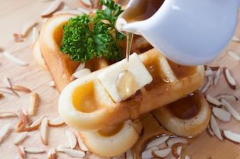 Close-up versando miele dalla parte superiore di waffle e dado che ha prezzemolo e formaggio in cima a cialde su piastra di legno per la colazione.