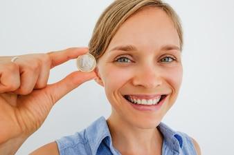 Closeup di donna sorridente che tiene una moneta dell'euro