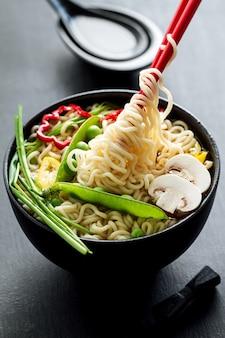 Closeup di gustoso zuppa di tagliatelle asiatiche appetitose con verdure. Avvicinamento. Tonificante.