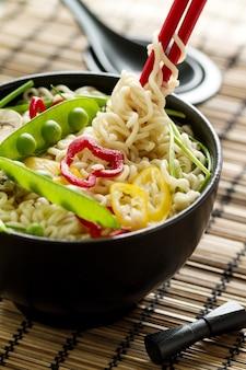 Closeup gustoso zuppa di tagliatelle asiatiche appetitose con verdure in ciotola di ceramica nera. Avvicinamento.