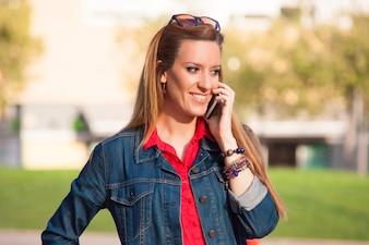 Closeup ritratto di ragazza divertente parlando al telefono in strada