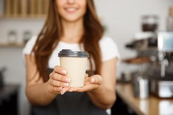 Coffee Business Concept - Bella signora caucasica sorridente alla fotocamera offre prelibatezza prendere il caffè caldo presso il caffè moderno