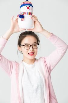 Colpo in studio della giovane donna asiatica con un pupazzo di neve di Natale