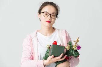 Colpo in studio della giovane donna asiatica con un regalo di Natale