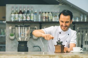Colpo interno di giovane barista maschio facendo una tazza di caffè mentre sta dietro il bancone del caffè. Giovane, versando, latte, in, à, tazza, di, caffè.
