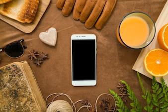 Composizione con telefono cellulare e succo d'arancia per il giorno del padre