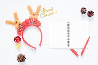 Composizione di Natale. Decorazioni natalizie, coni di pino, taccuino e penna rossa con spazio di copia. Piatto piano, vista dall'alto