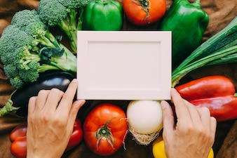 Composizione di verdure con mani e cornice