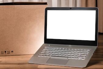 Computer portatile con schermo vuoto sul tavolo di legno e sfondo sfocato
