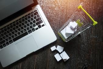 Computer portatile schermo vuoto e hopping carrello pieno di regali con copyspace, concetto di shopping online.