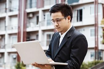 Concetto Business - asiatico bello uomo d'affari che lavora sull'investimento di proprietà con il computer portatile.