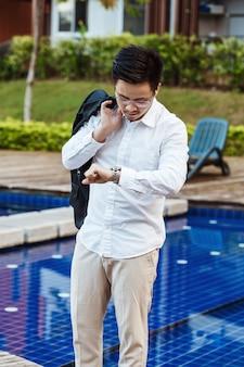 Concetto di affari - Giovane uomo d'affari che controlla tempo per la riunione.