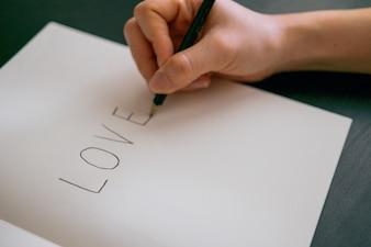Concetto di amore - mano scrivere amore sul libro