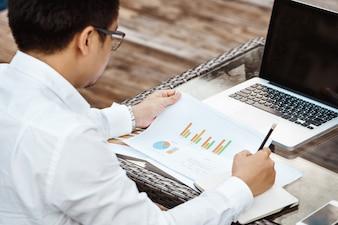 Concetto di Business - Giovane uomo d'affari che woking sul piano finanziario. Analisi della strategia.