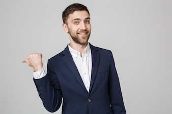 Concetto di business - ritratto giovane imprenditore di successo che punta il dito su sfondo scuro. Copia spazio.
