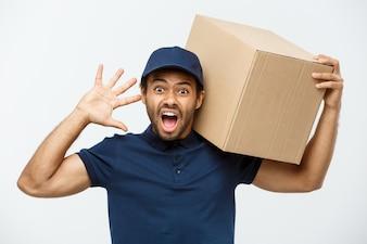 Concetto di consegna - Ritratto di Serio uomo di consegna afro-americano mostrando espressione sciocca aggressiva con la tenuta di un pacchetto di scatola. Isolato su sfondo grigio dello studio. Copia spazio.