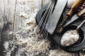 Concetto di cottura cucinare cucina cucchiai accessori per la cottura su fondo in legno con farina. Vista dall'alto. Processo di cottura. Nessuno.