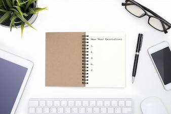 Concetto di risoluzioni di nuovo anno con la scrivania bianca