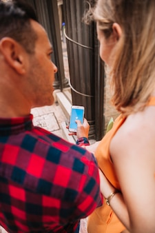 Concetto di shopping con coppia guardando smartphone