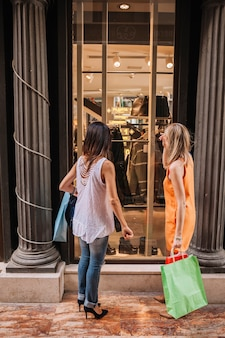 Concetto di shopping con la donna di fronte al negozio