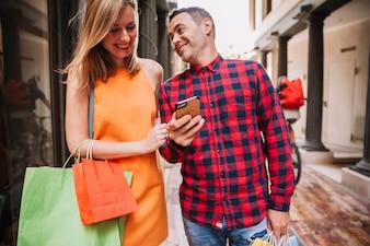 Concetto di shopping con smartphone di coppia azienda