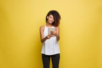 Concetto di stile di vita - Ritratto di bella donna afroamericana gioiosa giocando qualcosa su tavoletta elettronica. Sfondo di studio pastello giallo. Copia spazio.