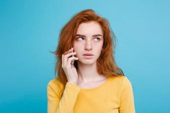 Concetto di stile di vita - Ritratto di ragazza di capelli rossi zenzero con espressione scioccante e stressante mentre parla con l'amico dal telefono cellulare. Isolato su sfondo blu pastello. Copia spazio.