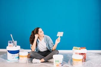 Concetto di vernice con la donna guardando pennello