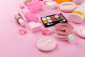 Concetto femminile di bellezza di bellezza. Diversi compongono cosmetici essenziali di bellezza su sfondo rosa. Vista dall'alto. Composizione laterale.
