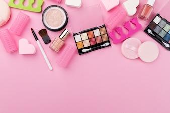 Concetto femminile di bellezza di bellezza. Diversi compongono cosmetici essenziali di bellezza su sfondo rosa. Vista dall'alto. Sopra.
