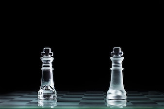 Confrontazione - due re scacchi in legno che si levano in piedi uno contro l'altro su una scacchiera.