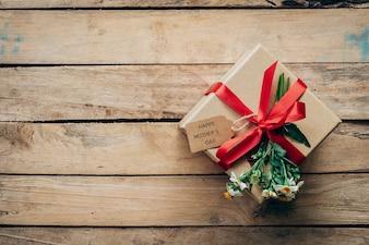 Contenitore di regalo marrone e fiore sul tavolo di legno presente, concetto di giorno della madre.