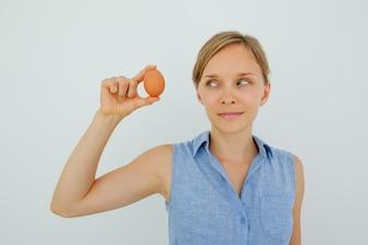 Contenuto Donna Holding Uovo Con Due Dita