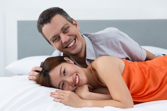 Coppia allegra rilassante in letto comodo