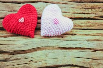 Coppia di cuore crochet in rosso e rosa su sfondo di legno. La foto è focalizzata al cuore rosso.