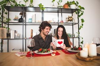 Coppia seduta a un tavolo per mangiare, mentre lei legge una cartolina romantica e sorride