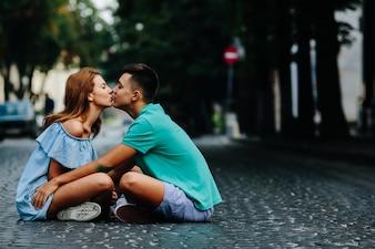 Coppia seduta sulla strada strada baciare