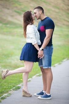 Coppie che baciano in un campo verde e lei con una gamba