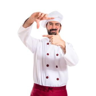 Cuoco concentrando con le dita su uno sfondo bianco