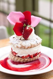 Deliziosa torta di fragola con una bella tazza sulla piastra bianca