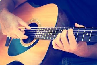 Dettagli di esecutore uomo mani suonare la chitarra acustica musical, foto retrò d'epoca