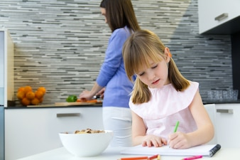 Disegno a bambino con pastelli, seduto a tavola in cucina a casa