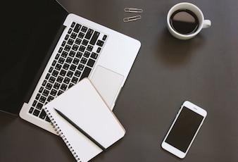 Disegno pianeggiante piatto creativo dello scrittorio dello spazio di lavoro con il computer portatile, il taccuino, lo smartphone ed il caffè con lo spazio della copia dello spazio