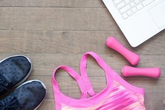 Disegno pianeggiante piatto creativo di concetto di sport e fitness su sfondo di legno con il computer portatile