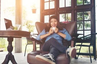 Donna, alzando con una tazza di caffè, sorride disteso sul divano, divano.
