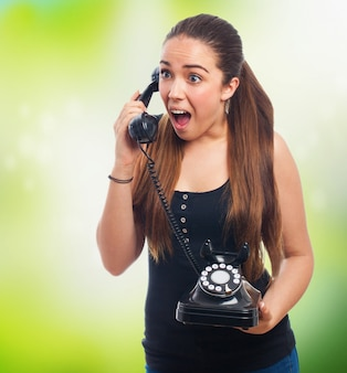 Donna arrabbiata a parlare su un telefono antico