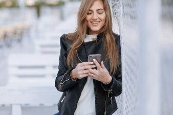 Donna che esamina il suo smartphone e sorride
